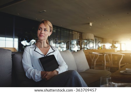 Thoughtful young female holding touch pad with blank copy space screen for your text message while sitting in restaurant, woman luxury coffee shop owner with digital tablet waiting for her new clients - stock photo