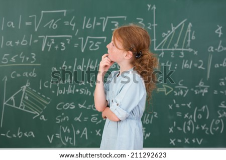 Thoughtful young girl in mathematics class standing sideways looking up at a blackboard covered in equations with her hand to her chin as she seeks an answer to a problem - stock photo