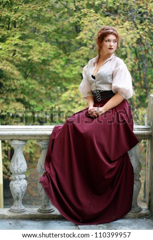 thoughtful Young lady in old fashion dress outdoor sitting - stock photo