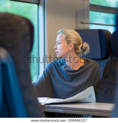 Thoughtful young lady reading while traveling by train. - stock photo