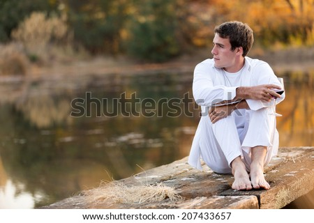 thoughtful young man drinking wine alone by a lake - stock photo