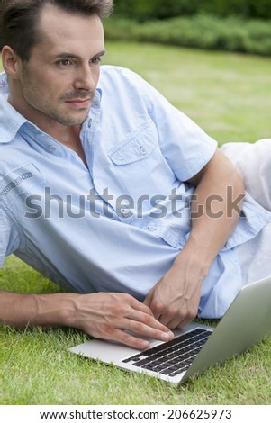 Thoughtful young man with laptop in park - stock photo