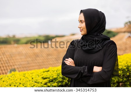 thoughtful young muslim woman with arms crossed - stock photo