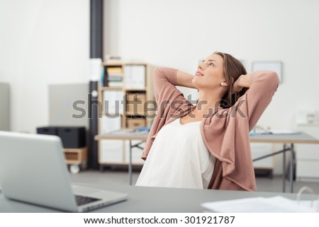 Thoughtful Young Office Girl Relaxing at her Workplace While Leaning her Back on a Chair and Looking Up with Both Hands Holding Behind her Head - stock photo