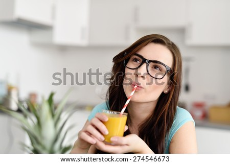 Thoughtful Young Pretty Woman with Eyeglasses Drinking a Glass of Orange Juice Using Straw While at the Kitchen. - stock photo