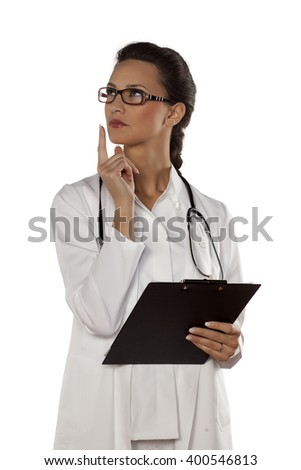 thoughtful young woman doctor on a white background - stock photo