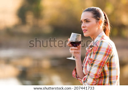 thoughtful young woman holding wine glass outdoors in autumn - stock photo