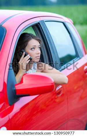 Thoughtful young woman in a car talking by cellphone - stock photo