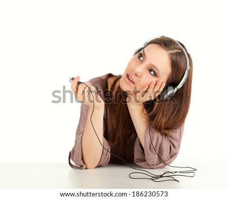 thoughtful young woman listening to music, white background - stock photo
