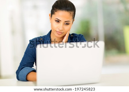 thoughtful young woman looking at the laptop screen - stock photo