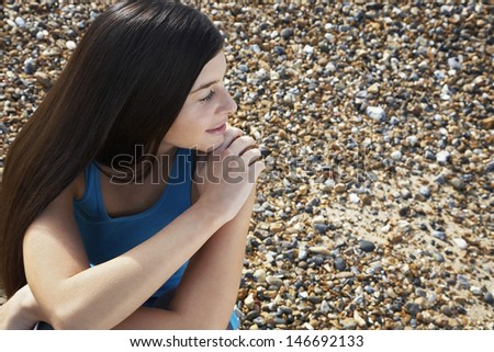 Thoughtful young woman looking away while sitting at beach - stock photo