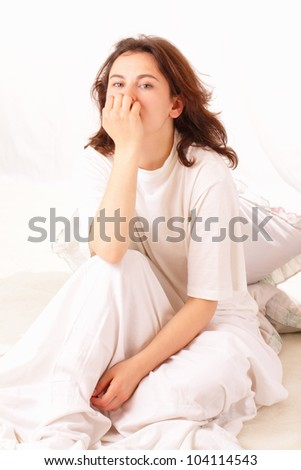 Thoughtful young woman relaxing in bed - stock photo