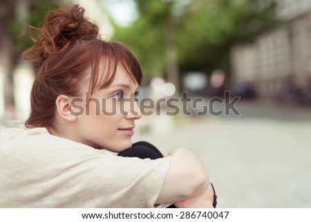 Thoughtful young woman sitting hugging her knees as she sits staring thoughtfully into the air, profile view in an urban street - stock photo