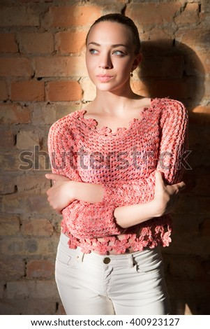 Thoughtful young woman wearing knitted sweater and white pants posing near brick wall - stock photo