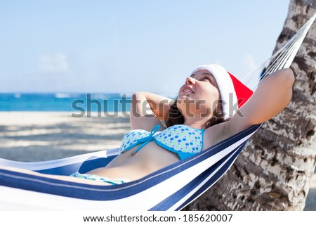 Thoughtful young woman wearing Santa hat in hammock at beach - stock photo