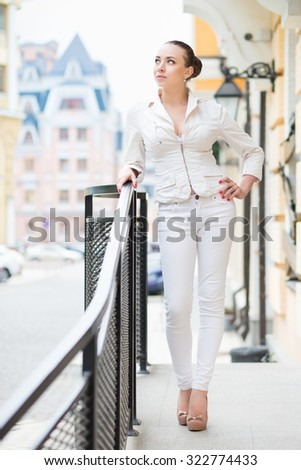 Thoughtful young woman wearing white pants and jacket posing outdoors - stock photo