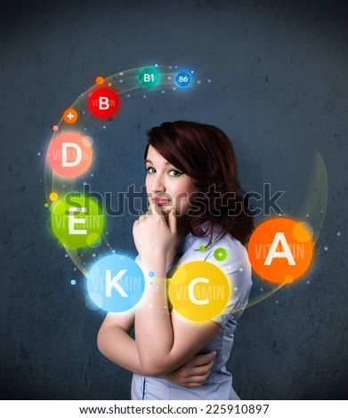 Thoughtful young woman with vitamin icons circulating around her head - stock photo