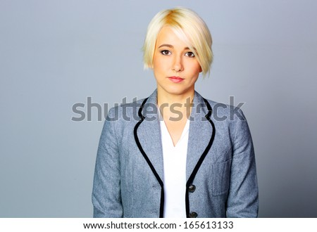 Thoughtfull businesswoman in gray jacket standing on gray background - stock photo