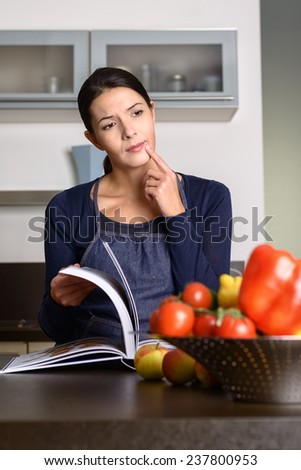 Thougthful middle-aged Woman Wearing Apron reading a Recipe Book at the Kitchen counter - stock photo