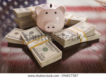 Thousands of Dollars and Piggy Bank with Reflection of American Flag on Table. - stock photo
