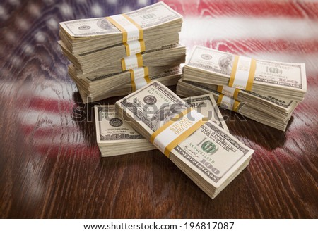 Thousands of Dollars Stacked with Reflection of American Flag on Wooden Table. - stock photo