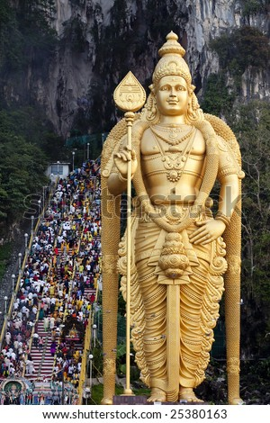Thousands of Hindu Tamil Indians climbing steps to Batu Caves alongside statue of Lord Murugan in Kuala Lumpur, Malaysia for Thaipusam - stock photo