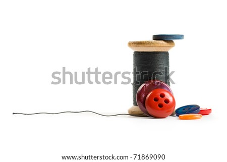 Thread bobbin and buttons isolated on white background - stock photo