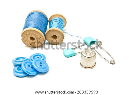 thread, buttons and thimble on white background - stock photo