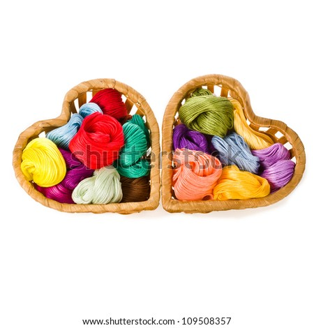 thread for embroidery cross in two wicker baskets in the shape of the heart, isolated on white background - stock photo