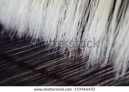 Thread on the traditional weaving machine - stock photo