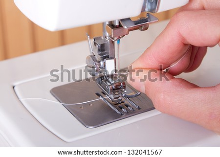 Threading a sewing machine hands showing - stock photo