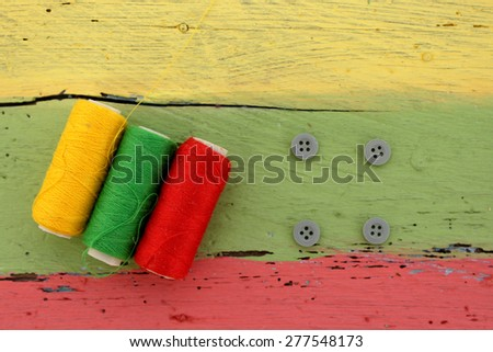 Threads and buttons, reggae colors - stock photo