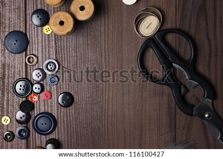 threads buttons and needles on brown wooden table - stock photo