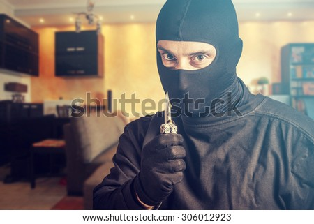 Threatening burglar holding a knife. Cross processed image for dramatic look - stock photo