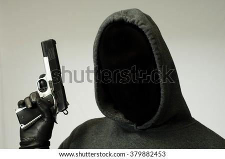 Threatening thug holds a gun - stock photo