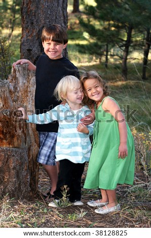 three adorable children in outdoor setting - stock photo