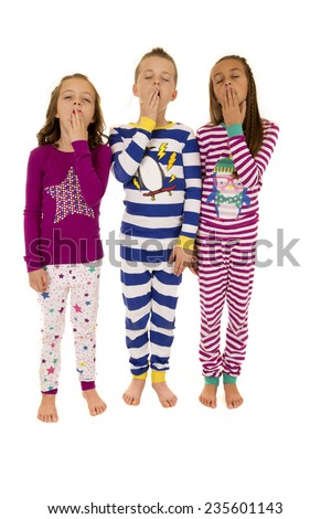 three adorable children wearing winter pajamas yawning - stock photo