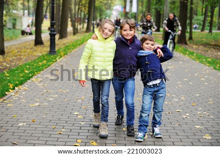 Three adorable fashionable children two school aged girls and a boy have fun during the walk on the beauty autumn dai in the park - stock photo