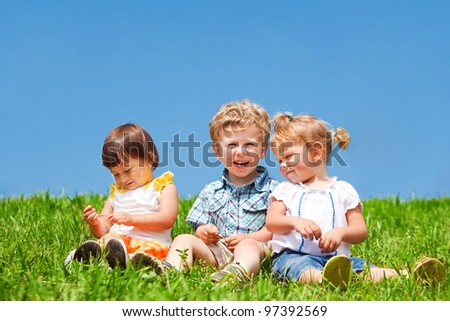 Three adorable kids sit on green grass against blue sky - stock photo
