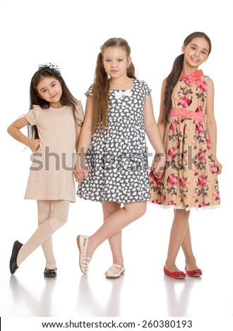 three adorable little girls holding hands - isolated on white. - stock photo