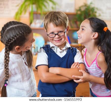 Three adorable schoolchildren having fun in classroom - stock photo