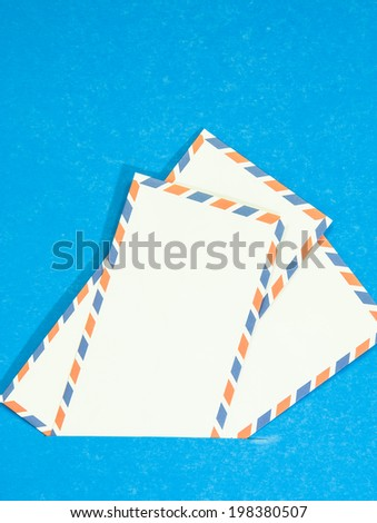 Three Air mail envelope interpolate on blue background. - stock photo