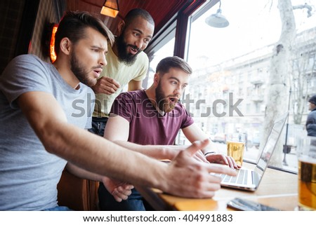 Three amazed shocked handsome men watching video on laptop together and shouting in cafe - stock photo