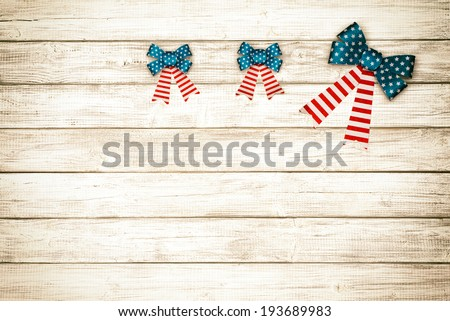Three American Flag Bows Lined up on Rustic White or Gray Wood Board Background with room or space for copy, text.  Horizontal with old fashioned, sepia treatment - stock photo