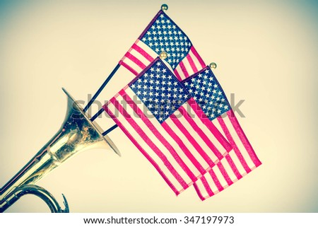 Three American Flags erupt from the bell of a trumpet in patriotism image - stock photo