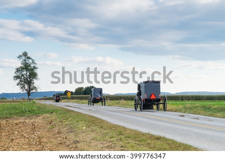 Three amish carriages along a rural road in Lancaster County, Pennsylvania - stock photo