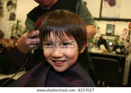 Three and half years old boy having a haircut - stock photo