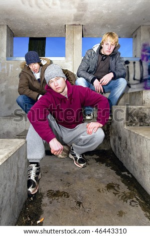 Three angry looking gang members in a dirty, concrete bunker at dusk. - stock photo