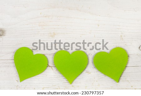 Three apple green hearts on old white shabby style wooden background. - stock photo