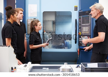 Three Apprentices Working With Engineer On CNC Machinery - stock photo